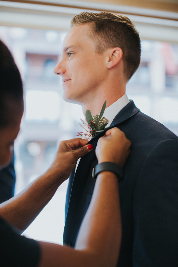wedding planning, pinning the groom's boutonniere, wedding day, real colorado weddings, Rembrandt yard boulder